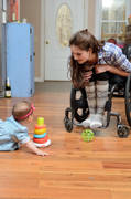 Young-woman-using-wheelchair-playing-with-her-baby