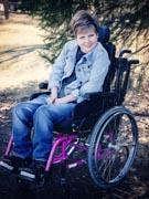 Teenage-girl-sitting-in-wheelchair-under-tree-in-park