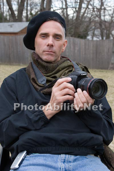 Portrait of a disabled male photographer in a wheelchair