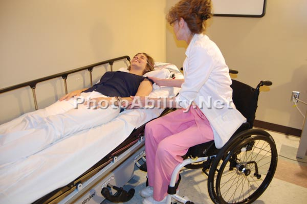 Female doctor in a wheelchair with her patient in an examination room