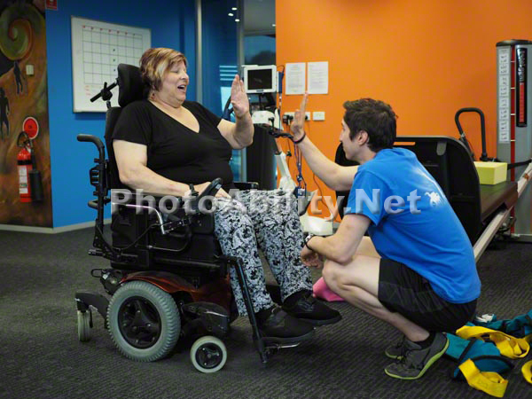 Two Male Physical Therapists Giving Treatment To A Woman With A Disability