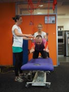 Two-Female-Physical-Therapists-Giving-Treatment-To-A-Man-With-A-Disability