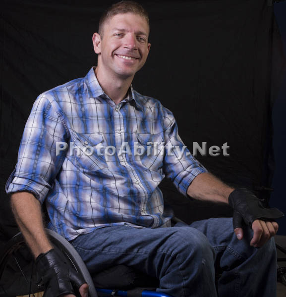 Portrait of a man using a wheelchair against a black background