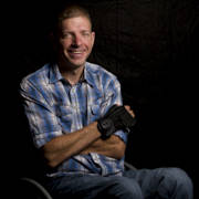 Portrait-of-man-using-wheelchair-against-black-background