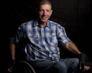 Portrait-of-man-using-wheelchair-against-black-background