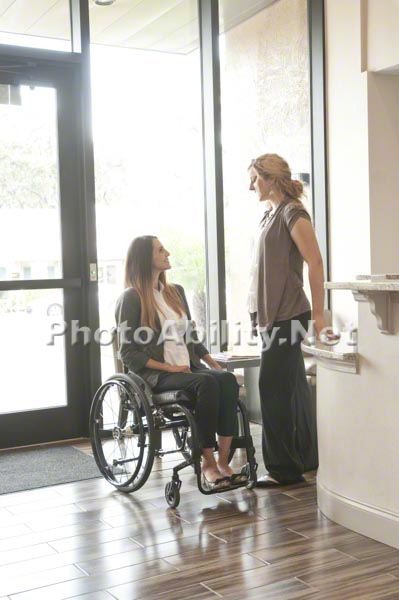 Young professional woman in a wheelchair in an office