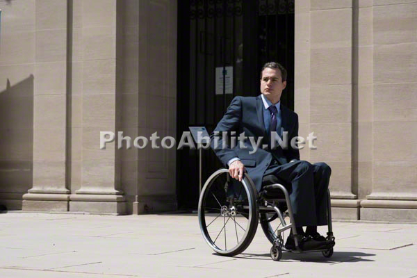 Young businessman in a suit and tie using a wheelchair