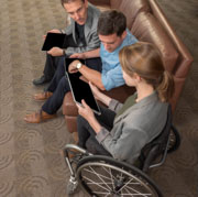 Young-woman-in-wheelchair-in-discussion-with-colleagues-using-tablets