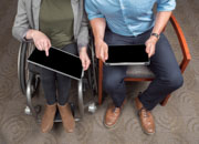 Young-business-woman-in-wheelchair-in-discussion-with-colleague-using-tablets