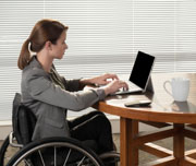Young-woman-in-wheelchair-using-her-laptop-in-an-office
