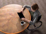 Young-woman-in-wheelchair-using-her-tablet-in-an-office