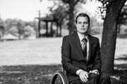 Young-businessman-in-suit-and-tie-using-wheelchair