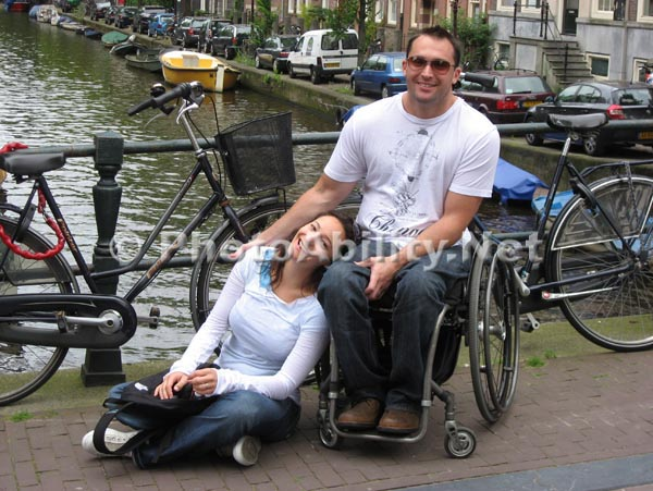 Amsterdam;couple;wheelchair;male;traveling;tourist;canal;bridge;smiling;fun;bikes