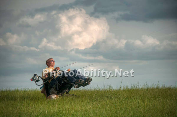Man using a power wheelchair flying a kite