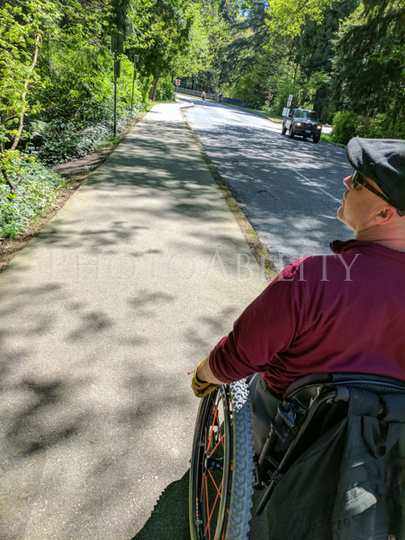 Man using a wheelchair on a suburban footpath