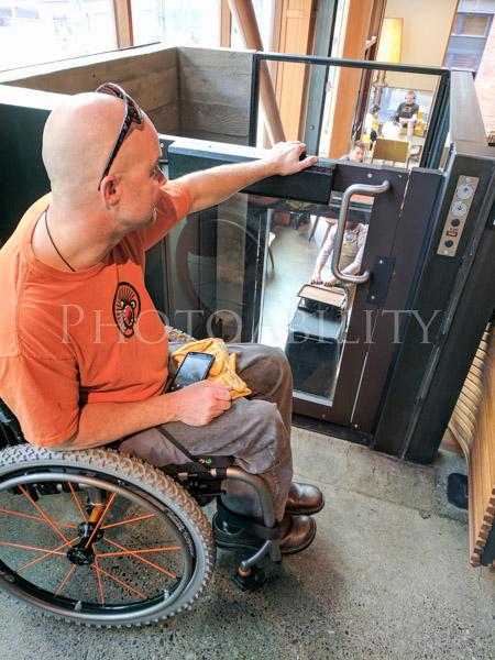 Man using a wheelchair using a wheelchair elevator