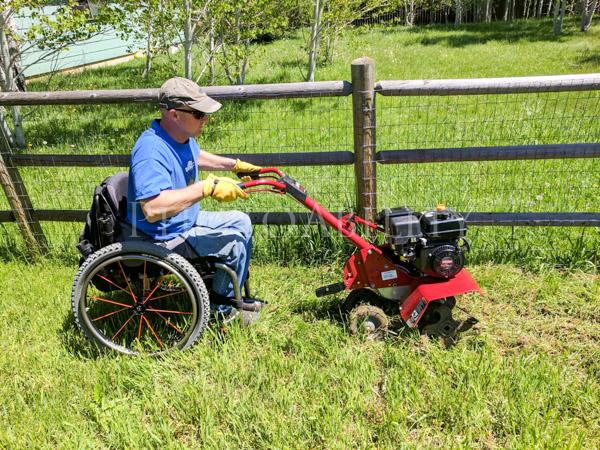 Man using a wheelchair using a rotary hoe