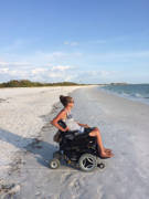 Young-woman-using-power-wheelchair-on-an-ocean-beach