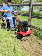 Man-using-wheelchair-tilling-his-garden-with-rotary-hoe