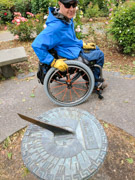 Man-using-wheelchair-looking-at-garden-sundial