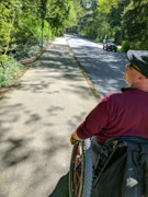 Man-using-wheelchair-on-suburban-footpath