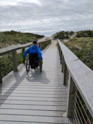 Man-using-wheelchair-on-an-accessible-beach-boardwalk
